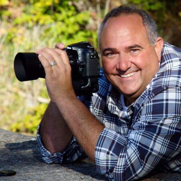 Dr. Gregory R. Liberatore, dentist in Ballston Spa, NY, posing outside with his camera
